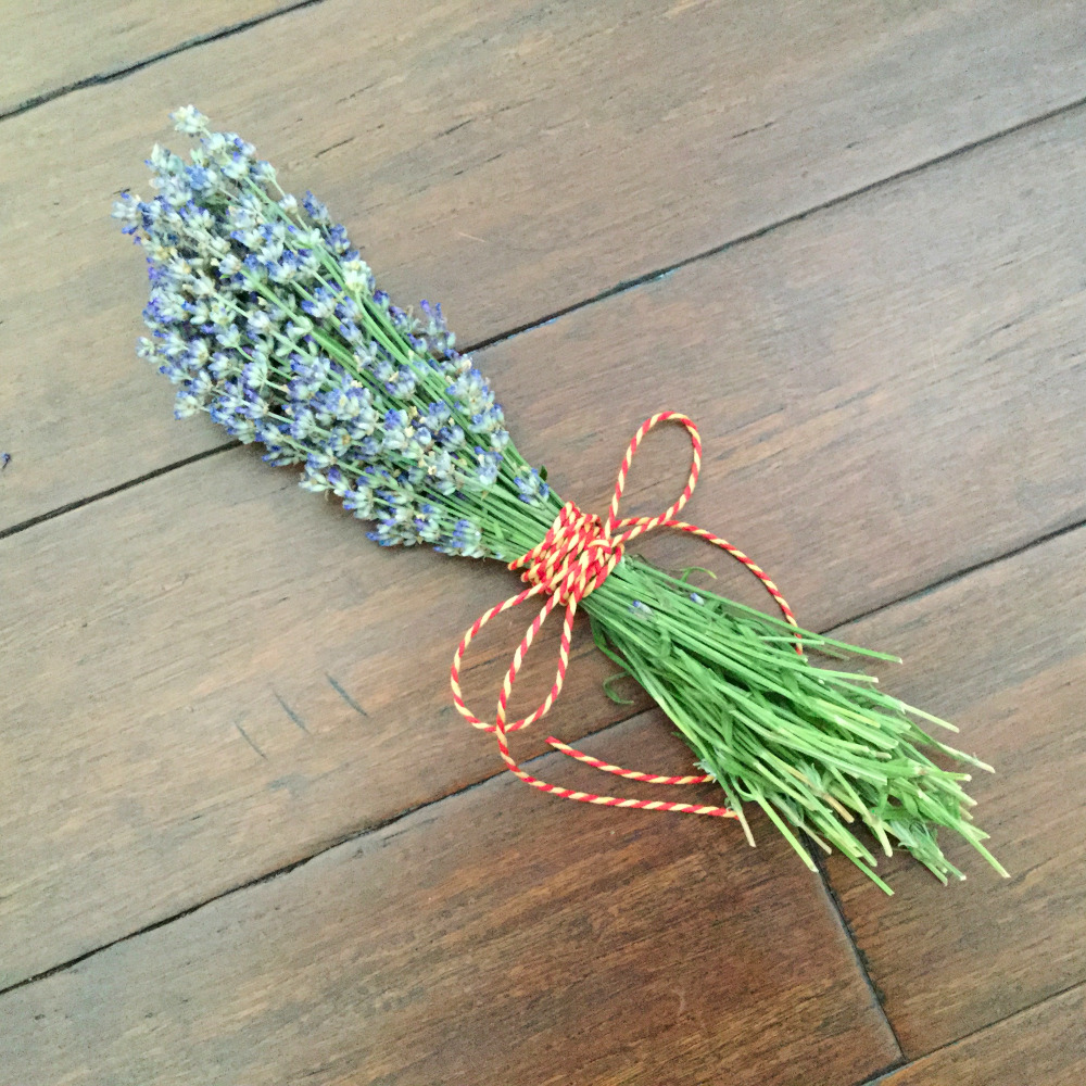 Lavender bundle ready to be dried sitting on a wooden table