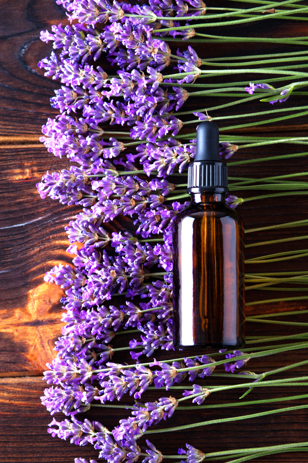 homemade lavender linen spray sitting on a wood table with fresh lavender sprigs
