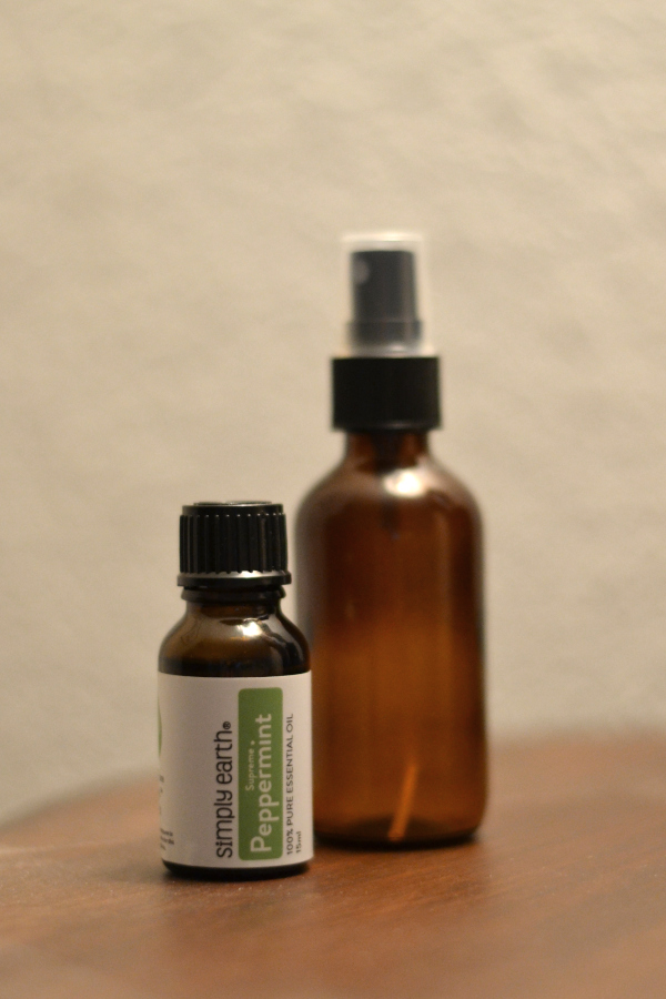 peppermint essential oil and glass bottle sitting on a table