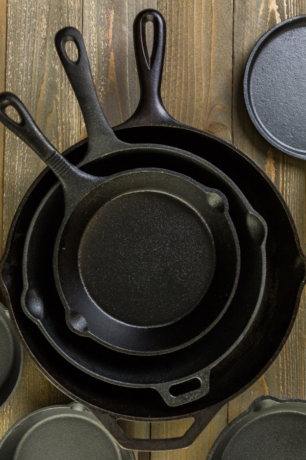 recently seasoned cast iron pans stacked in a pile on a wooden table.