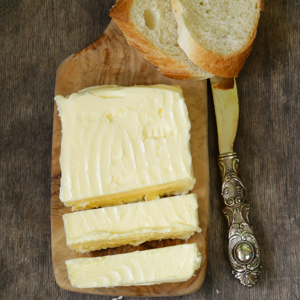 homemade butter on a cutting board with bread.