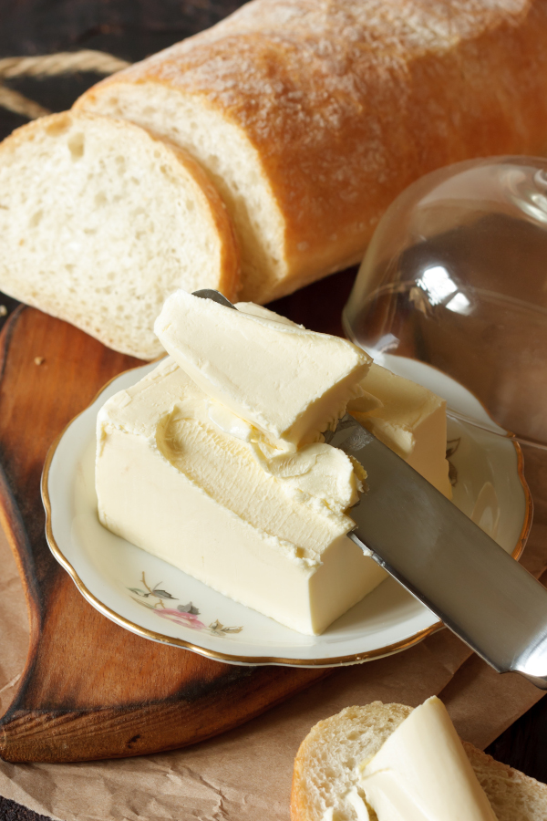 homemade butter being spread on bread with a knife.