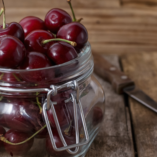 cherries sitting on a jar on the table