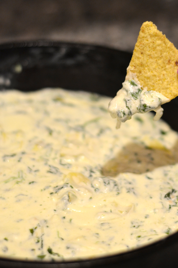 homemade spinach artichoke dip baked in a dutch oven cast iron pan.