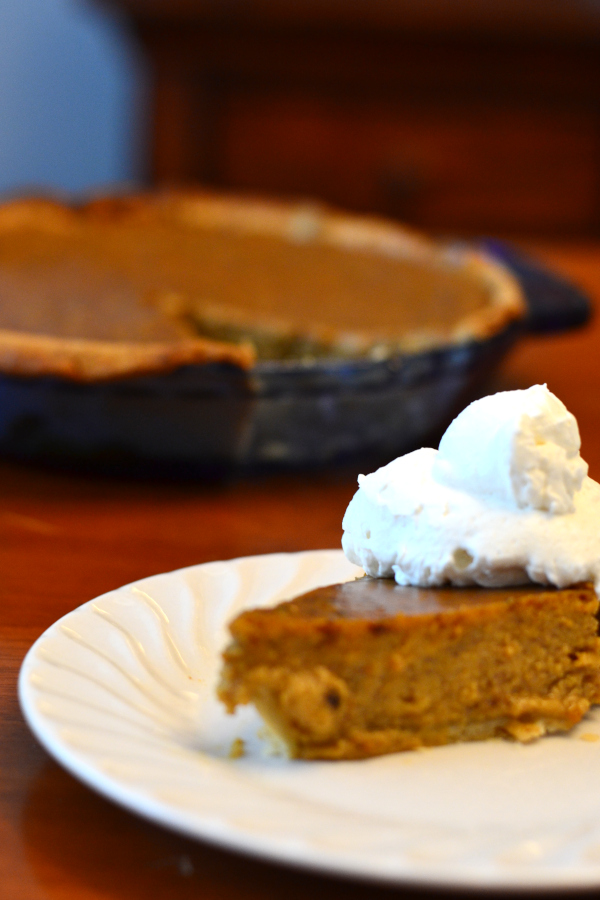 a slice of spiced pumpkin pie with homemade whipped cream.