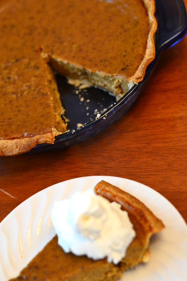 freshly baked spiced pumpkin pie with one slice of pie.