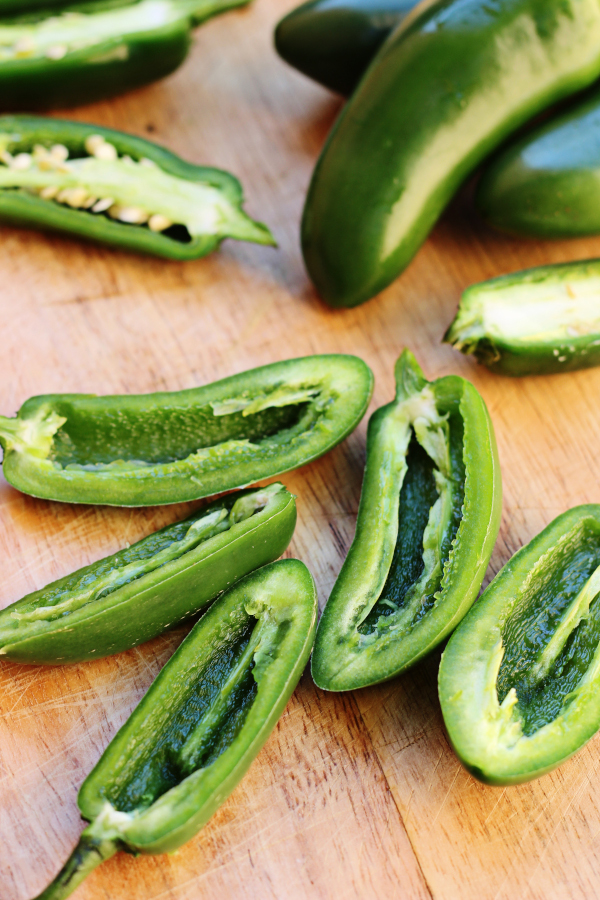sliced jalapenos sitting on a wooden cutting board.