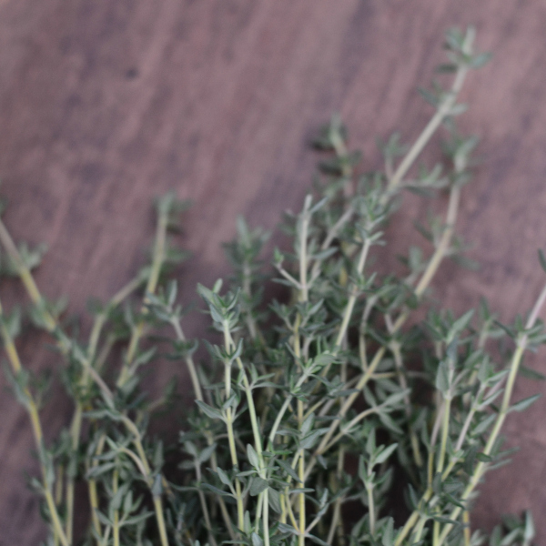 freshly harvested thyme sitting on a wooden table