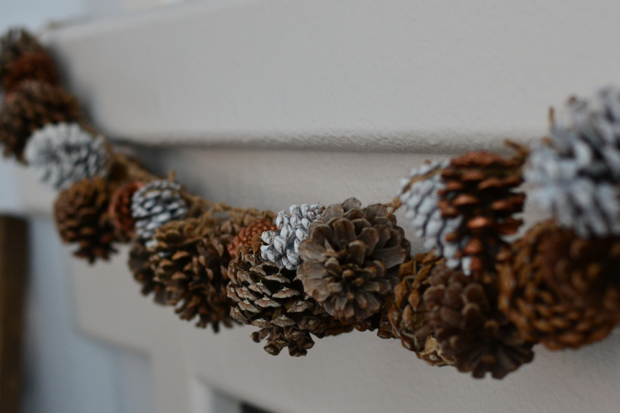 beautiful pine cone garland handmade on a fireplace mantle.