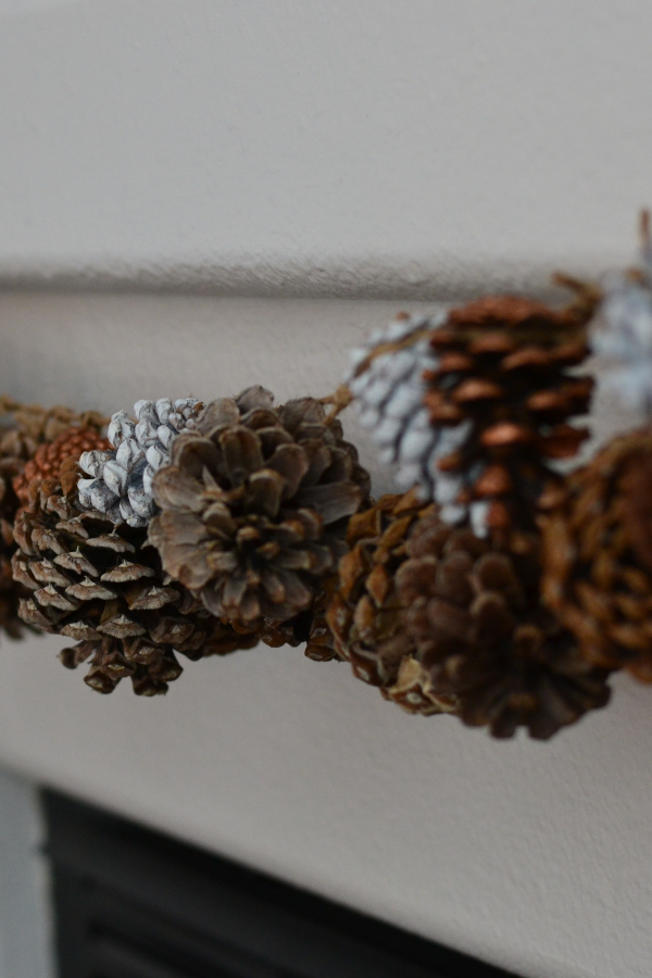 handmade DIY pinecone garland hanging on a fireplace mantle.