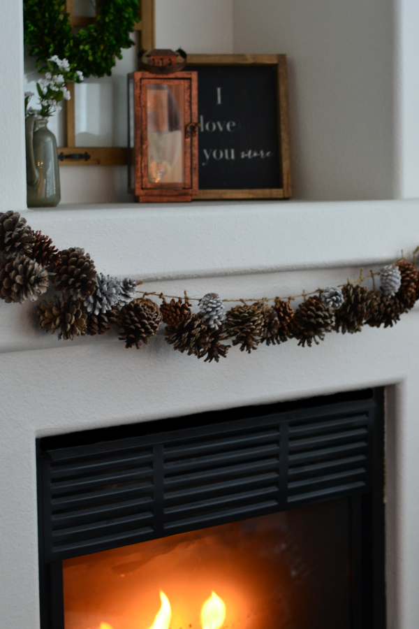 homemade pinecone garland hanging on a fireplace mantle