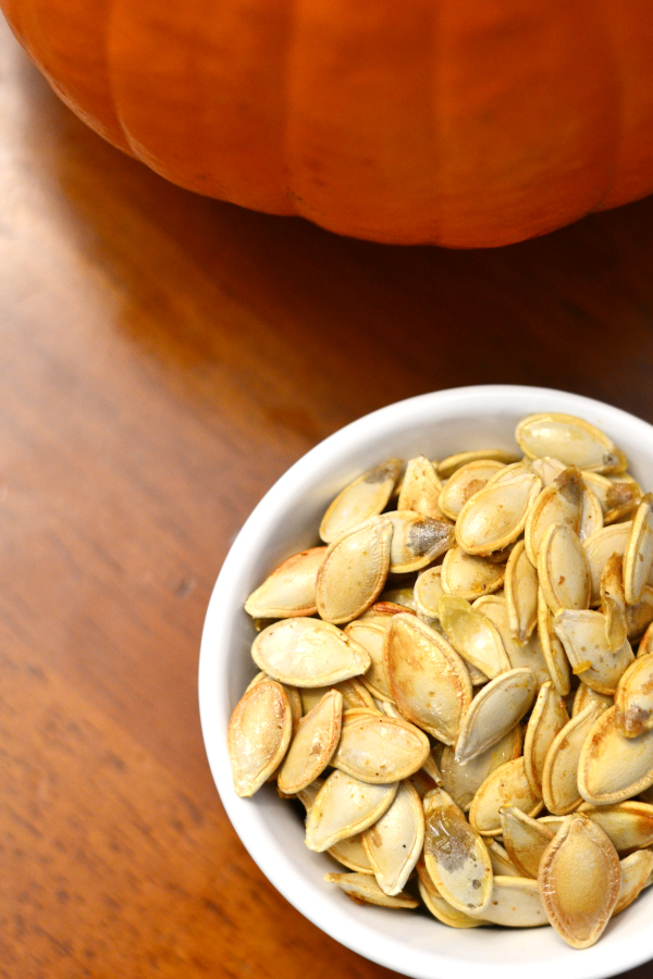 Freshly homemade roasted pumpkin seeds in a bowl on a kitchen table.