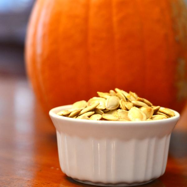 Freshly roasted pumpkin seed recipe sitting next to a pumpkin.