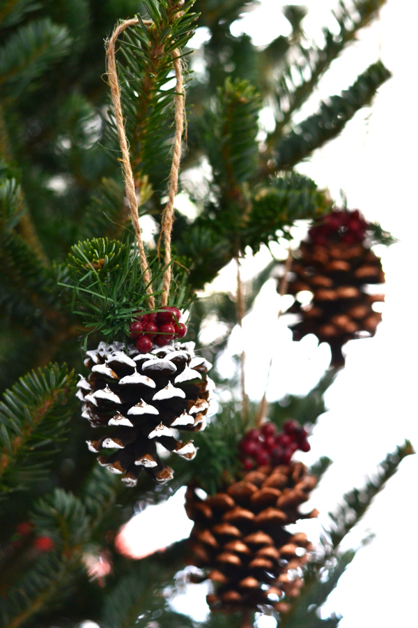 DIY homemade pinecone ornament hanging on a Christmas tree.