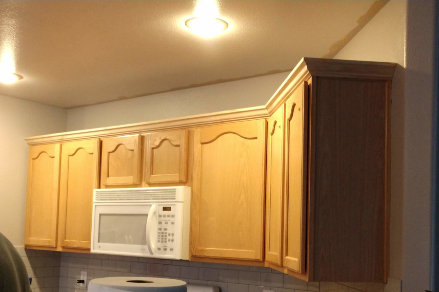 adding crown molding to the cabinets in a kitchen remodel