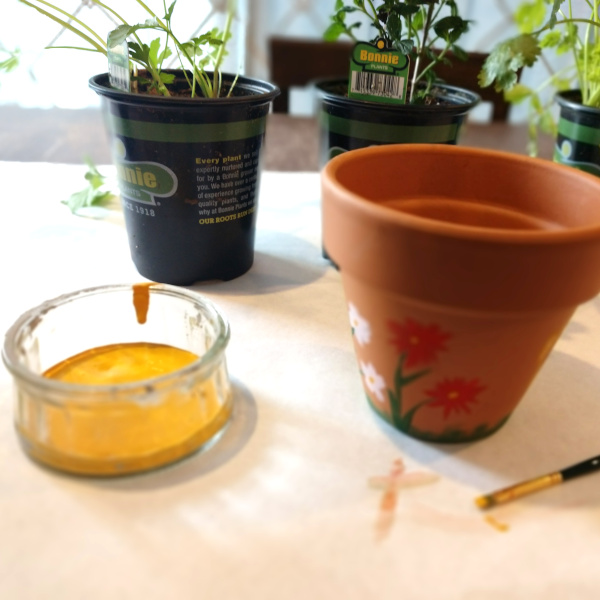chalk painting the terra cotta pots on a table