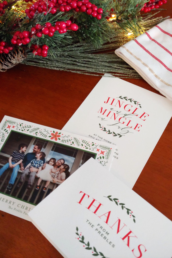 christmas card, invitations and thank you card sitting on a table decorated for Christmas