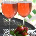 strawberry white wine spritzer and strawberries sitting on a table outside
