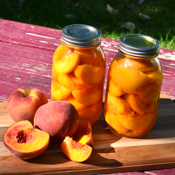 two jars of canned peaches sitting on a table