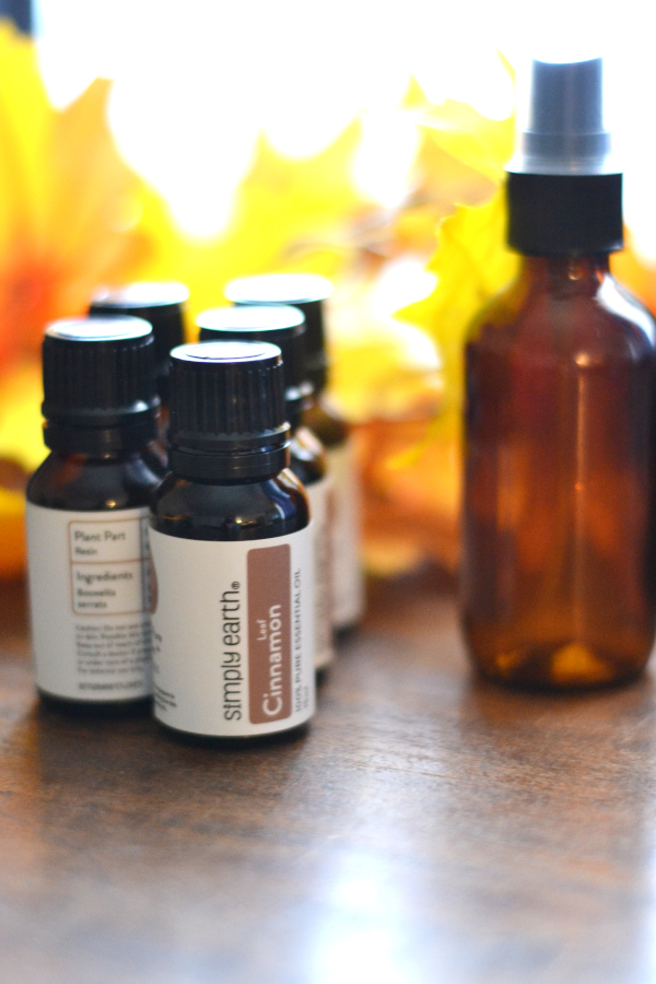 essential oils and fall leaves sitting on a table