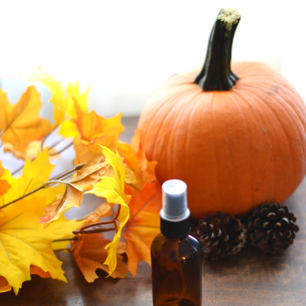 fall room spray and pumpkin on a table