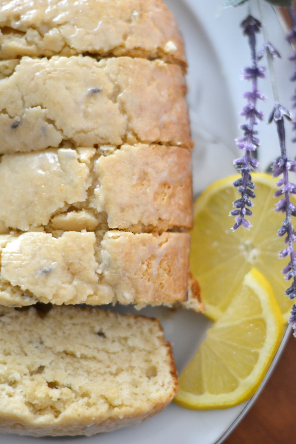 lavender tea bread with a lemon glaze on a plate on a table.