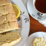 Lavender tea bread on a plate with black tea and fresh lemon.
