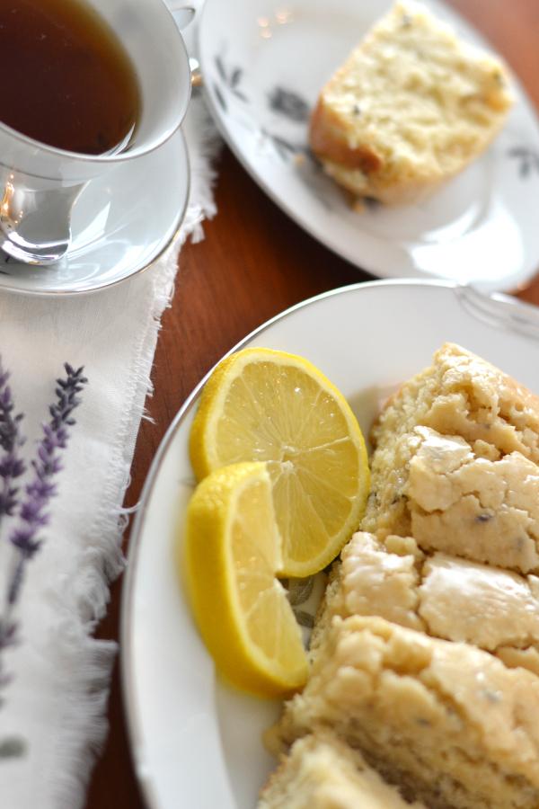 lavender tea bread with lemon glaze and fresh lemons on a table.