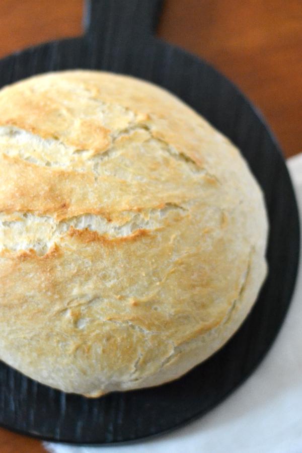 Homemade easy bread recipe anyone can bake sitting on a cutting board.