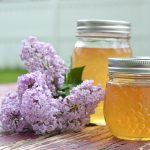 Homemade lilac jelly sitting on a table next to fresh lilac flowers.