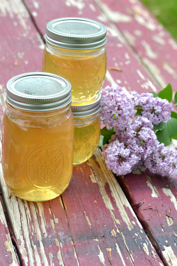 Water-bath canned lilac jelly in mason jars sitting next to fresh lilac flowers.