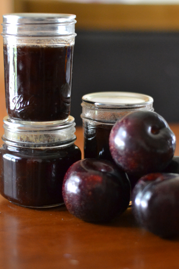 Three jars of spiced plum jam and fresh plums sitting on a table.