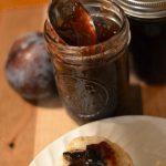 spiced plum jam in a mason jar with a spoon.