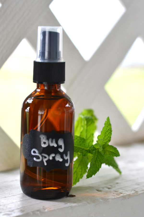 Homemade bug repellant sitting on the sill of a terrace with fresh peppermint.