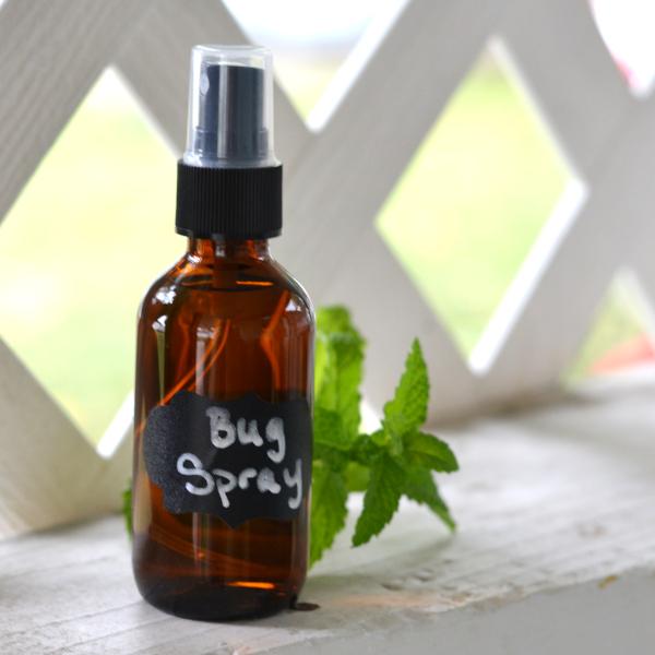 Homemade bug spray in an amber bottle sitting on a white terrace shelf.
