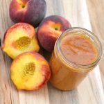 Homemade slow cooker peach butter in a glass mason jar next to fresh peaches.