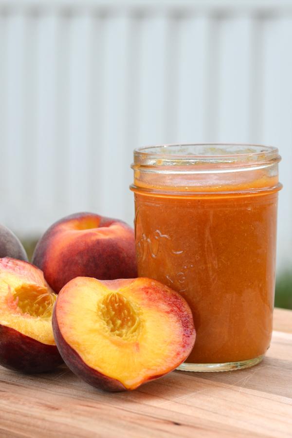 Easy crock pot peach butter recipe in a mason jar sitting on a table.