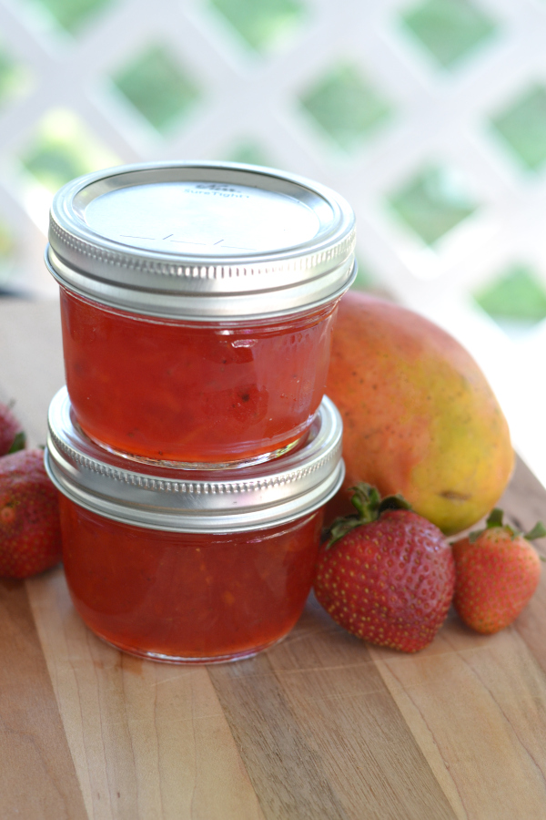 Homemade strawberry mango jam in small mason jars sitting on an outdoor table
