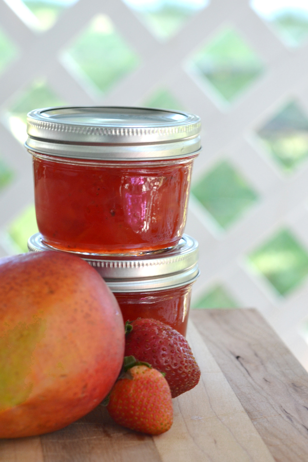 Strawberry and mango jam water-bath canned on an outdoor table.